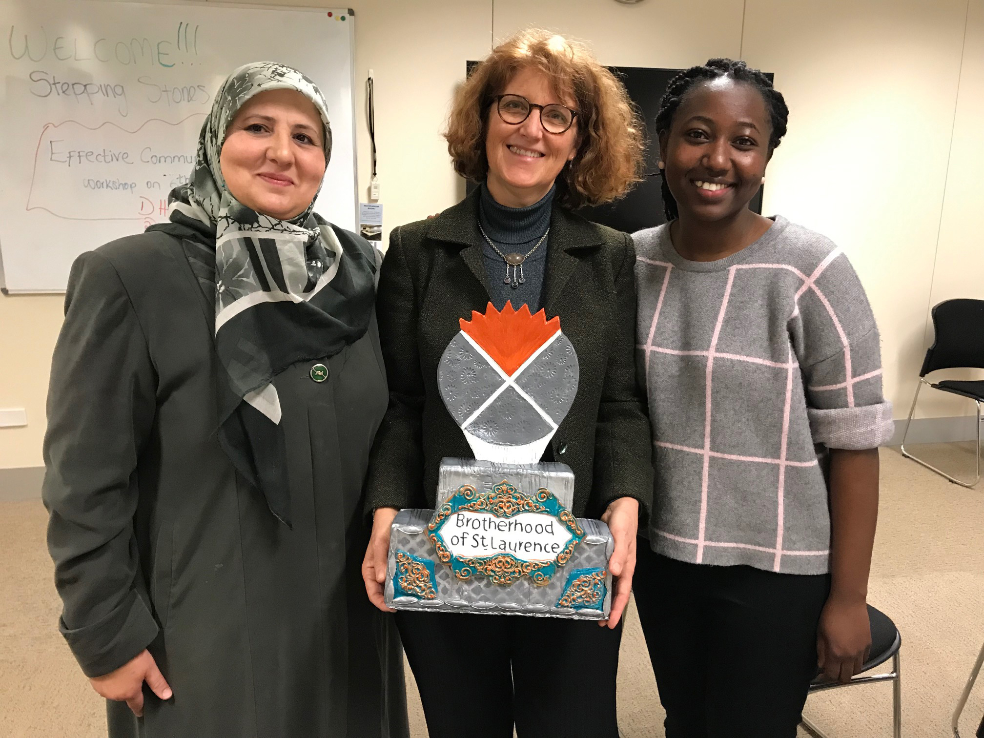 Linet and Meredith from our Multicultural Communities team with Ahlam who started her own business, Cookies by Dreams, through our Stepping Stones to Small business program, and made this incredible, edible trophy for the team.