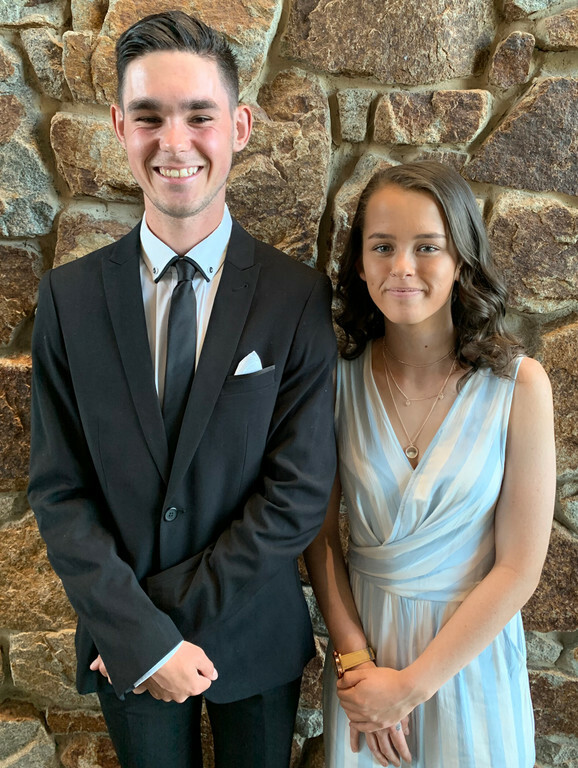 Two smiling young students dressed formally