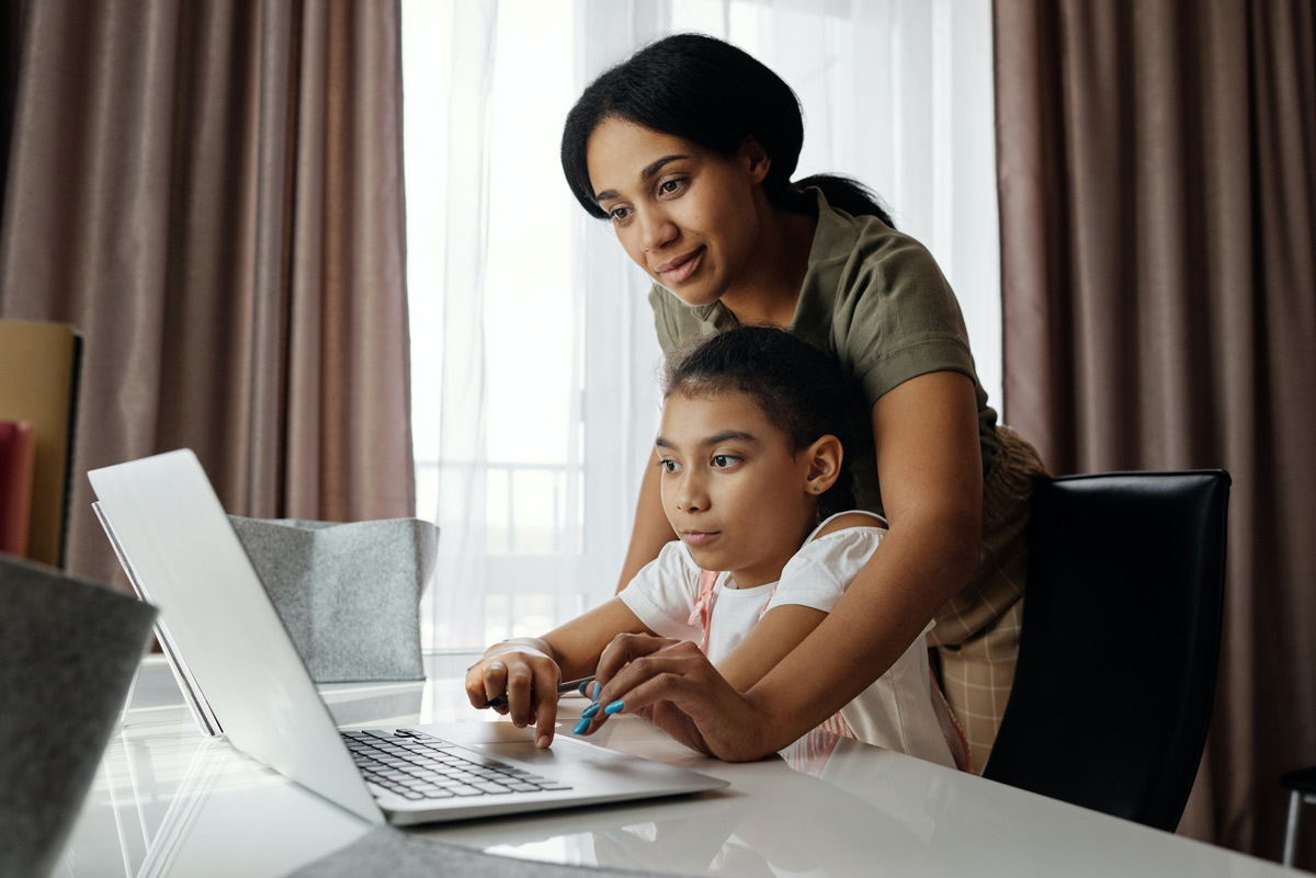 A young girl works on a laptop while her mother helps